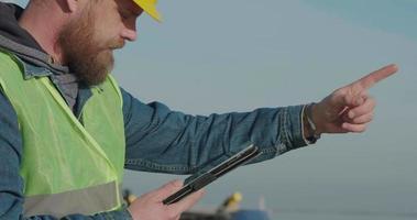 travailleur portuaire de portrait avec une barbe dans un casque jaune video