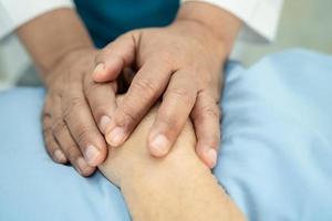 médico sosteniendo las manos conmovedoras anciana asiática o anciana paciente con amor, cuidado, ayuda, aliento y empatía en la sala del hospital de enfermería, concepto médico saludable foto