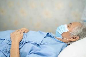 paciente mujer asiática se acuesta con máscara para proteger la infección de seguridad brote de coronavirus covid-19 en la sala del hospital de enfermería de cuarentena. foto