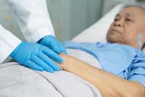 médico tomados de la mano anciana asiática mayor o anciana mujer infectada paciente con amor, cuidado, ayuda, aliento y empatía en la sala de cuarentena brote de coronavirus covid-19 en la sala del hospital de enfermería. foto