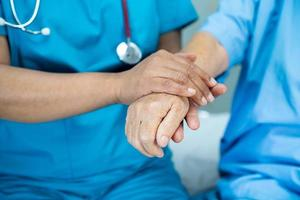 Tomados de la mano anciana asiática o anciana paciente con amor, cuidado, ánimo y empatía en la sala del hospital de enfermería, concepto médico fuerte y saludable foto