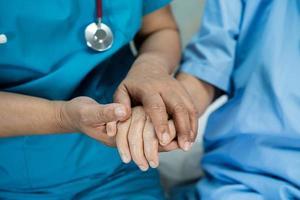 médico tomados de la mano anciana asiática anciana o anciana paciente con amor, cuidado, ánimo y empatía en la sala del hospital de enfermería, concepto médico saludable foto