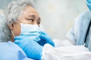 médico que usa un estetoscopio para verificar que el paciente asiático mayor o anciano usa una mascarilla en el hospital para proteger la infección por el coronavirus del covid 19. foto