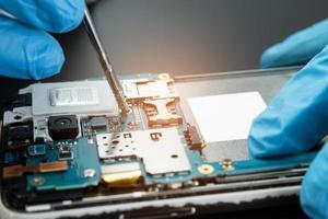 técnico que repara el interior del disco duro con un soldador. circuito integrado. el concepto de datos, hardware, técnico y tecnología. foto