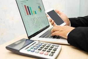 Asian accountant working and analyzing financial reports project accounting with chart graph and calculator in modern office, finance and business concept. photo