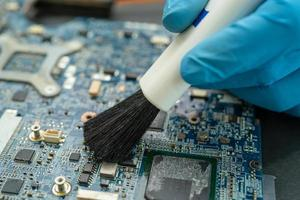 Technician use brush and air blower ball to clean dust in circuit board computer. Repair upgrade and maintenance technology. photo