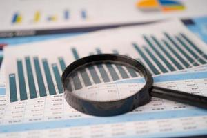 Magnifying glass on spreadsheet charts graphs paper. Financial development, Banking Account, Statistics, Investment Analytic research data economy, Stock exchange trading, Business office company meeting concept. photo