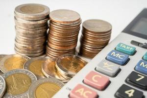 Coins on calculator and graph  paper. Finance development, Banking Account, Statistics, Investment Analytic research data economy, Stock exchange trading, Business company concept. photo