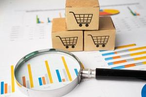 Shopping cart logo on box with magnifying glass on graph background. Banking Account, Investment Analytic research data economy, trading, Business import export transportation online company concept. photo
