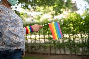 Asian lady holding rainbow color flag, symbol of LGBT pride month celebrate annual in June social of gay, lesbian, bisexual, transgender, human rights. photo