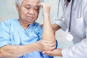 Asian senior or elderly old lady woman patient feel pain her elbow on bed in nursing hospital ward, healthy strong medical concept. photo