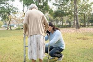Ayude y cuide a la anciana asiática mayor o anciana que use un andador con una salud fuerte mientras camina en el parque en felices vacaciones frescas. foto