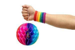 Señora asiática que lleva pulseras de la bandera del arco iris que sostienen la bola colorida de las flores del papel del panal aislar en el fondo blanco con el trazado de recorte, símbolo del mes del orgullo lgbt. foto