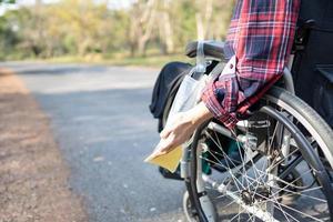 Paciente mujer asiática dama de mediana edad sentado en silla de ruedas con bolsa de orina en la sala del hospital, concepto médico saludable foto