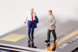 La gente en miniatura del hombre de negocios está parado en la tarjeta de crédito, concepto de las finanzas del negocio de la gestión. foto