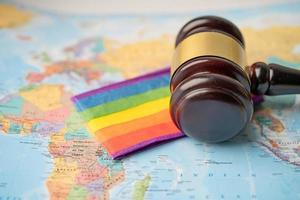 Bangkok, Thailand - December 1, 2020 LGBT rainbow flag with gavel for judge lawyer on world globe map. photo