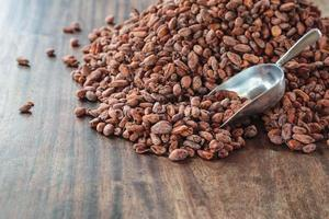 Raw cocoa beans on a wooden table photo