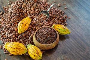 cocoa nibs and cocoa fruit on wooden table photo