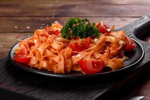Deliciosa pasta fresca con salsa de tomate con especias y hierbas sobre un fondo oscuro foto