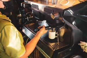 Barista, asian woman Brewing coffee with a coffee machine. For starting a small business in food industry concept. photo