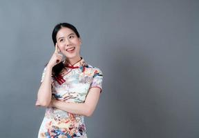 Hermosa joven asiática vistiendo traje tradicional chino con la mano que presenta en el lateral foto