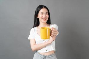 joven, mujer asiática, con, cara feliz, y, mano, tenencia, taza de café foto