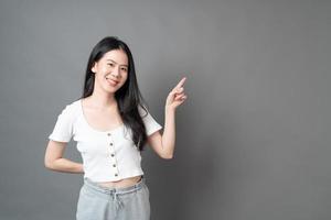 Mujer asiática con rostro sonriente y presentación de la mano en el lateral foto
