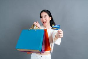 Beautiful Asian woman with shopping bags and showing credit card photo