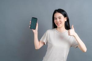Asian woman using mobile phone applications, enjoying communicating distantly online in social network or shopping photo