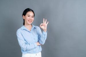 joven, mujer asiática, sonriente, y, actuación, señal ok foto