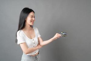 Mujer asiática con cara feliz y presentando tarjeta de crédito en mano mostrando confianza y seguridad para realizar el pago foto