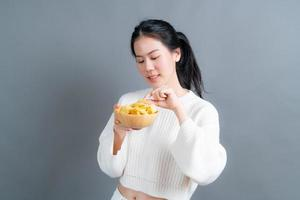 joven asiática comer papas fritas foto