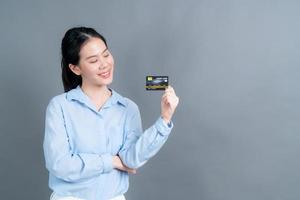 Portrait of a lovely young Asian woman showing credit card photo