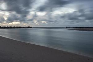 Estuario del río sventoji protegido por viejos rompeolas construidos con madera y piedras en la costa del mar Báltico de Lituania foto