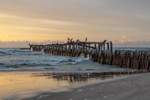 Hermosa playa de arena cerca del antiguo muelle rompeolas en uno de los balnearios más populares de Lituania foto