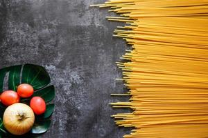 Yellow long spaghetti on a rustic background. Yellow italian pasta. Long spaghetti. Raw spaghetti bolognese. Raw spaghetti. Food background concept. Italian food and menu concept. photo