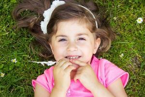 Little girl laying in the grass photo