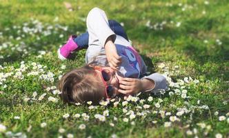 niña disfruta del día en el parque, recostada sobre el césped foto