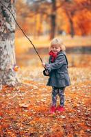 Beautiful little girl playing fishing with a branch and fish toy, in the park on a cold autumn day photo