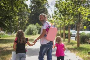 Father is taking his daughters to school, wearing kids schoolbag on his back photo