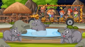 Safari en escena nocturna con niños viendo grupo de hipopótamos. vector
