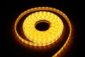 LED silicon shining strip in coil. Diode orange lights closeup photo