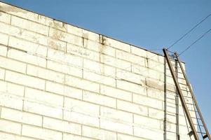 Modern warehouse building with an iron staircase casting shadow on te wahite wall photo