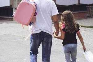 Father taking his daughter to school with copy space photo