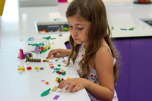 Cute little girl playing with construction toy blocks building a house  children and toys photo