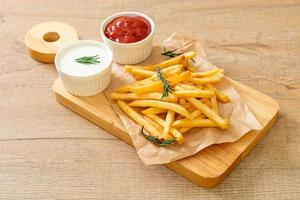 papas fritas con crema agria y salsa de tomate foto