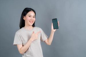 Mujer asiática que usa aplicaciones de teléfonos móviles, disfruta de la comunicación a distancia en línea en una red social o de compras. foto