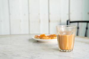 Vaso de té con leche tailandesa caliente en la mesa foto