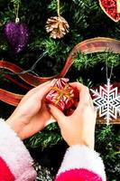 Hand holding Christmas ornament in front of Christmas tree photo