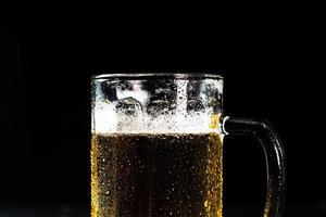 Vaso de cerveza con espuma de cerveza sobre fondo oscuro foto